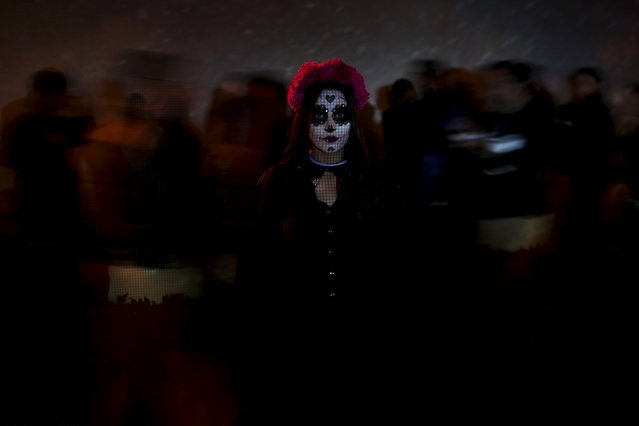 """A woman with her face painted as the popular Mexican figure """"Catrina"""" poses for a photograph during Day of the Dead celebrations in Ciudad Juarez, Mexico, November 2, 2015. The character """"Catrina"""", also known as the """"The Elegant Death"""", was created by Guadalupe Posada in the early 1900s and has become an important part of Mexico's celebrations of the Day of the Dead on November 1 and 2. (Photo by Jose Luis Gonzalez/Reuters)"""