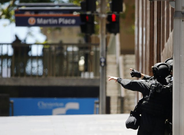 Police officers gesture near Lindt cafe in Martin Place, where hostages are being held, in central Sydney December 15, 2014. Dozens of hostages were trapped inside the central Sydney cafe on Monday, with local television showing some being forced to hold up a black flag with white Arabic writing in the window, raising fears of an attack linked to Islamic militants. (Photo by Jason Reed/Reuters)