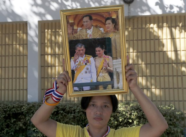 A supporter of the Thai monarchy holds aloft the images of late King Bhumibol Adulyadej and Queen Mother Sirikit and King Maha Vajiralongkorn and Queen Suthida near the parliament in Bangkok, Thailand, Tuesday, November 17, 2020. Thailand's political battleground shifted Tuesday to the country's Parliament, where lawmakers are considering proposals to amend the country's constitution, one of the core demands of the country's student-led pro-democracy movement. (Photo by Sakchai Lalit/AP Photo)