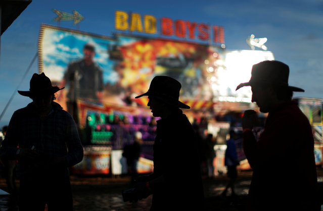 Men wearing Australian traditional bushmen's hats are silhouetted against colourful amusement rides in the late afternoon sun at the Deni Ute Muster in Deniliquin, New South Wales, Australia, October 1, 2016. (Photo by Jason Reed/Reuters)