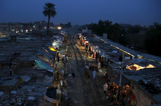 A view of the bazaar set up along the active railway line in Faqirabad outside Peshawar, Pakistan, October 16, 2015. (Photo by Khuram Parvez/Reuters)