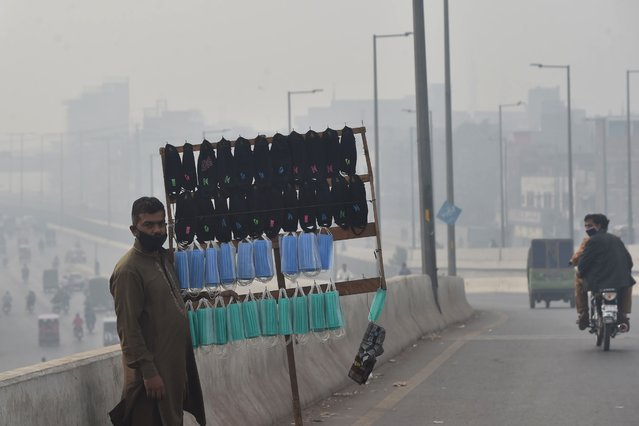 A vendor selling facemasks waits for customers on a bridge amid heavy smoggy conditions in Lahore on November 10, 2020. (Photo by Arif Ali/AFP Photo)