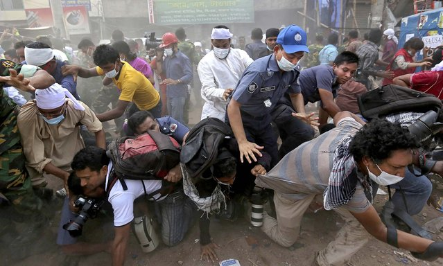 Rescue workers and journalists fall on top of each other in a stampede after the crowd panicked when someone shouted that another section of building might collapse on Friday. (Photo by Kevin Frayer/Associated Press)