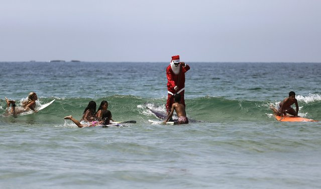 Carlos Bahia, dressed as Santa Claus, jokes with a child as they surf at the Maresias beach, in the state of Sao Paulo December 9, 2014. (Photo by Nacho Doce/Reuters)