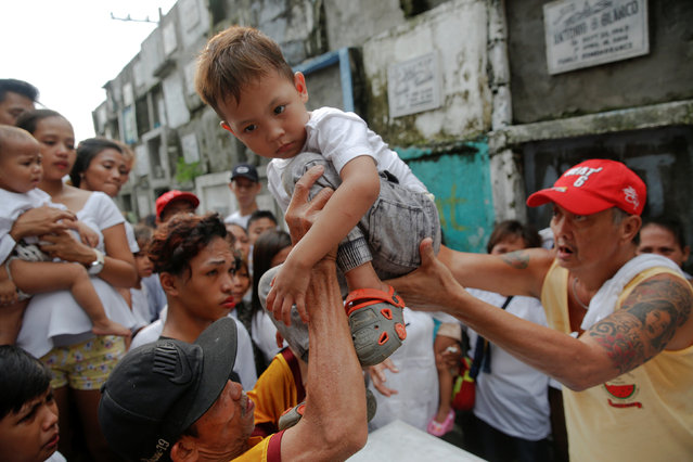 According to a local custom, a child is carried over the coffin during a funeral for two cousins killed by masked gunmen at a cemetery in Manila, Philippines October 11, 2016. (Photo by Damir Sagolj/Reuters)