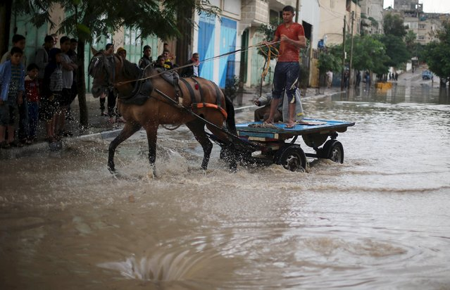 A Palestinian rides a horse cart along a street flooded by rain water in Khan Younis in the southern Gaza Strip, November 9, 2015. (Photo by Ibraheem Abu Mustafa/Reuters)