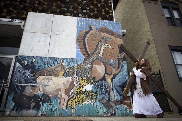 "Michael Grant, 28, ""Philly Jesus"", carries a 12 foot cross 8 miles past a mural depicting Noah's Ark in North Philadelphia towards LOVE Park in Center City as part of a Christmas walk to spread the true message of the holiday in Philadelphia, Pennsylvania December 20, 2014. (Photo by Mark Makela/Reuters)"