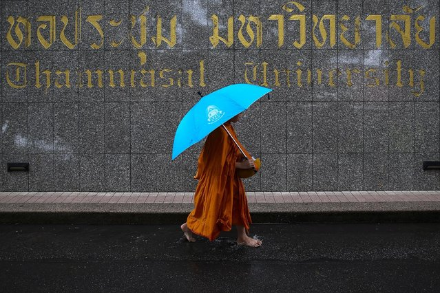 A buddhist monk walks after collecting alms during the 40th anniversary of a campus massacre by state forces in the military-ruled country at Thammasart University in Bangkok, Thailand. October 6, 2016. (Photo by Athit Perawongmetha/Reuters)