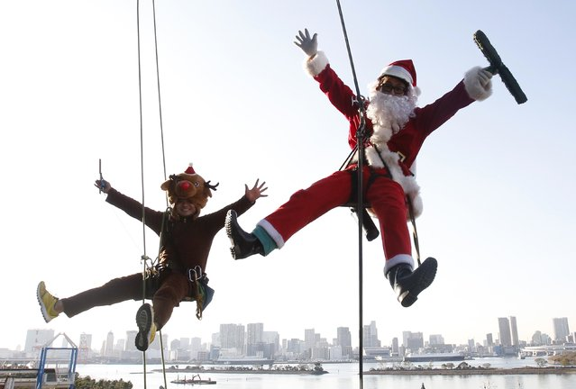 Window cleaners dressed as Santa Claus and a reindeer pose for pictures during an event to celebrate Christmas at a shopping mall in Tokyo December 24, 2014. (Photo by Yuya Shino/Reuters)