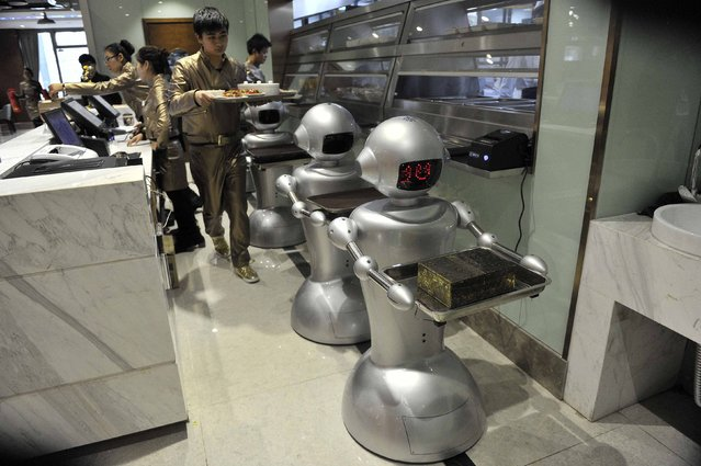 A man puts dishes on robots for delivery at a restaurant in Hefei, Anhui province, December 26, 2014. (Photo by Reuters/Stringer)