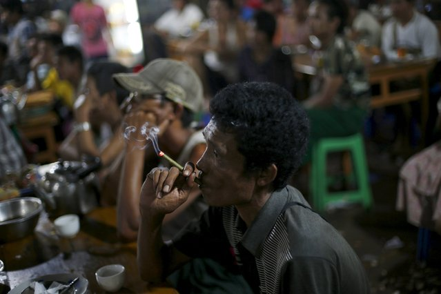 A man smokes while watching movies in a market in Yangon November 6, 2015. (Photo by Jorge Silva/Reuters)