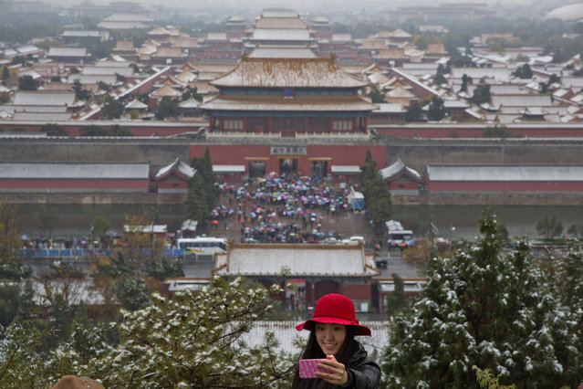 A woman takes a selfie near the Forbidden City coated white by winter's first snow fall in Beijing, China, Friday, November 6, 2015. (Photo by Ng Han Guan/AP Photo)