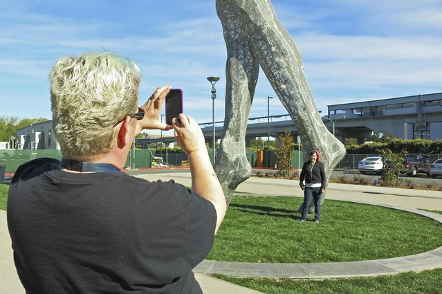 """In this photo taken Wednesday October 19, 2016, art teachers Jo Sutton, left, and Jennifer Jervis, right, take pictures beneath a 55-foot nude statue in San Leandro, Calif. The statue of a naked woman is stirring controversy and a lot of conversation. City officials and the sculptor of the steel nude, which was unveiled this week across from San Leandro's main commuter train stop, say they want to draw attention to """"feminine energy"""". Critics say the 13,000-pound towering nude is not appropriate public art. (Photo by Jocelyn Gecker/AP Photo)"""