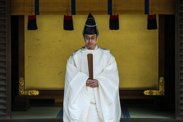 A Shinto priest conducts a ritual during ceremonies bidding farewell to 2014, ahead of New Year's Day, at the Meiji Shrine in Tokyo December 31, 2014. (Photo by Thomas Peter/Reuters)