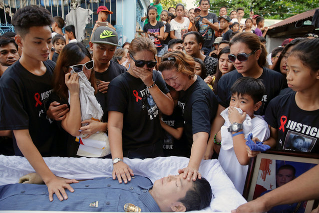Mother and other close relatives of Rancel Cruz, a police officer killed by an unknown gunman earlier this month, touch his body placed in a coffin, during the funeral in Manila, Philippines October 22, 2016. (Photo by Damir Sagolj/Reuters)