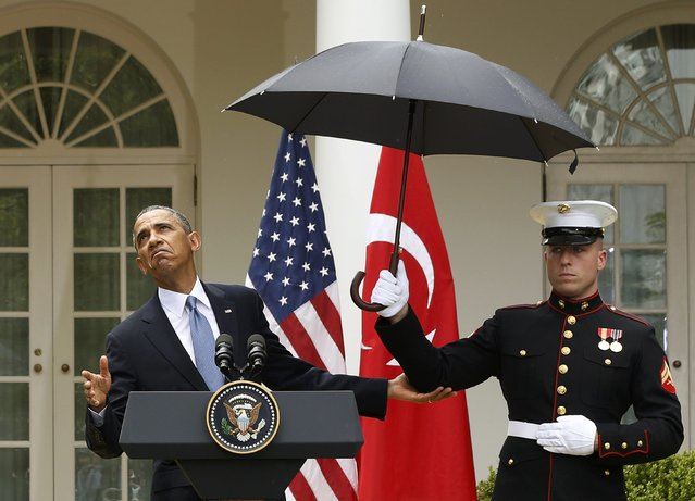U.S. President Barack Obama checks to see if he still needs the umbrella held by a U.S. Marine to protect him from the rain during a joint news conference with Turkish Prime Minister Recep Tayyip Erdogan in the Rose Garden of the White House  in Washington, May 16, 2013. (Photo by Jason Reed/Reuters)