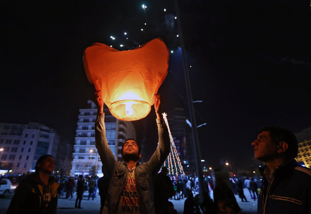 A  man holds a heart-shaped hot-air balloon during the New Year's celebrations in downtown Beirut, Lebanon, Thursday, January 1, 2015. (Photo by Bilal Hussein/AP Photo)