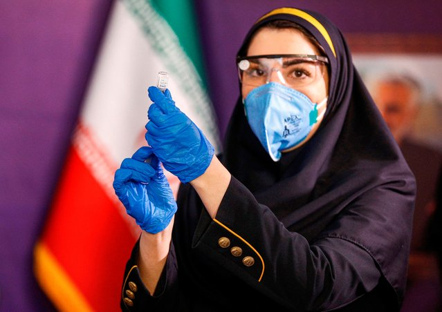 A health worker prepares an injection for a woman during the first trial phase of a locally-made Iranian vaccine for COVID-19 coronavirus disease in Iran's capital Tehran on December 29, 2020. (Photo by AFP Photo/Stringer)