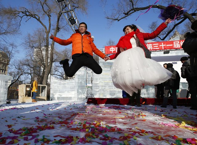 A newly wed couple jumps to pose for their wedding photographs after their group wedding ceremony which was held as part of the Harbin International Ice and Snow Festival in the northern city of Harbin, Heilongjiang province January 6, 2015. The wedding ceremony was organised by the city government and 11 couples from China, Russia and Egypt participated in the ceremony. (Photo by Kim Kyung-Hoon/Reuters)