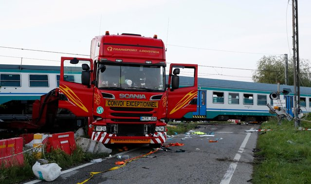 The wreckage of a truck sits next to a railroad crossing where it was hit my a regional train in Caluso, outside Turin, Italy, early Thursday, May 24, 2018. At least two were killed and over a dozen injured in the crash. (Photo by Antonio Calanni/AP Photo)