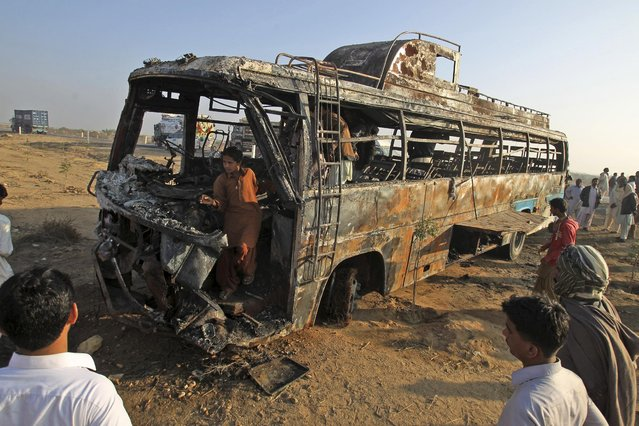 Pakistani gather around and inside the wreckage of a passenger bus that was destroyed after colliding with an oil tanker on a highway about 50 kilometers (31 miles) outside of Karachi, Pakistan, Sunday, January 11, 2015. More than 50 people were killed in the accident. (Photo by Fareed Khan/AP Photo)