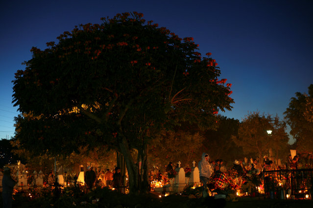 People visit a cemetery on the Day of the Dead by paying homage to their dead relatives, through the decoration of their graves, and the preparation of meals in Santa Maria Atzompa, Oaxaca, Mexico November 1, 2016. (Photo by Jorge Luis Plata/Reuters)