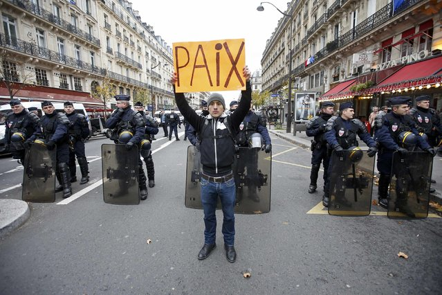 """A man holds a placard which reads """"Peace"""" in front of CRS riot policemen near the Place de la Republique after the cancellation of a planned climate march following shootings in the French capital, ahead of the World Climate Change Conference 2015 (COP21), in Paris, France, November 29, 2015. (Photo by Eric Gaillard/Reuters)"""