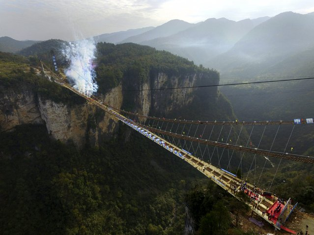 An aerial view shows fireworks going off to celebrate the completion of the construction of the steel box girder on a glass bridge as it suspends over a canyon in Zhangjiajie National Park, Hunan province, China, December 3, 2015. (Photo by Reuters/Stringer)