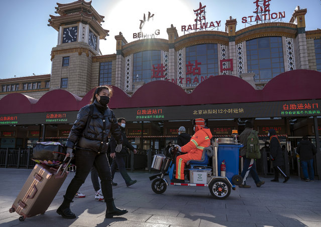 Travelers wearing face masks to protect against the spread of the coronavirus walk with their luggage at the Beijing Railway Station in Beijing, Thursday, January 28, 2021. (Photo by Mark Schiefelbein/AP Photo)