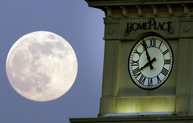 """A """"supermoon"""" rises behind the Home Place clock tower in Prattville, Ala., Saturday, June 22, 2013. (Photo by Dave Martin/AP Photo)"""