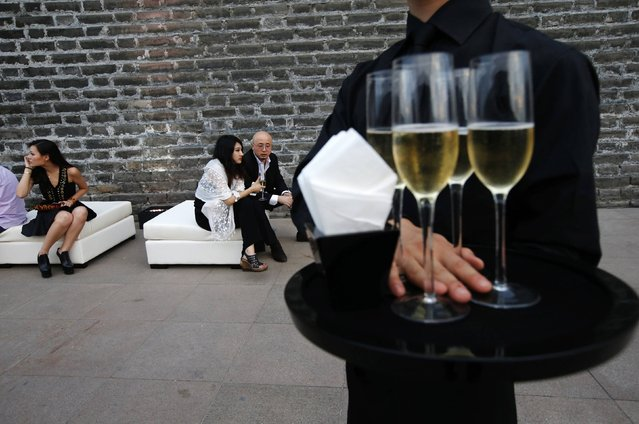 A bartender holds champagne for guests during a reception prior to a fashion show held at the Ming Dynasty City Wall Relics Park in Beijing in this June 21, 2013 file photo. An expected slowdown in growth of the world's second-largest economy means full-year growth would undershoot the government's 7.5 percent target and mark the weakest expansion in 24 years. (Photo by Kim Kyung-Hoon/Reuters)
