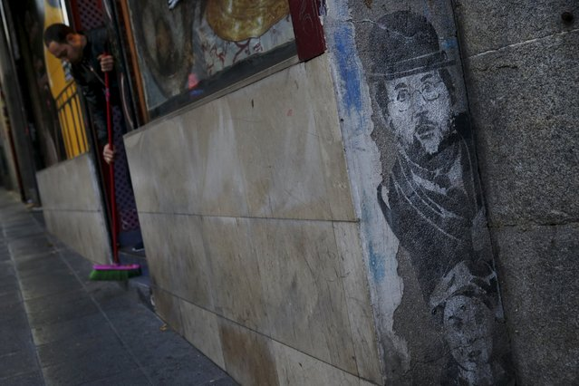 A worker sweeps the entrance steps to a restaurant next to a graffiti of Spanish Prime Minister Mariano Rajoy in Madrid, Spain, December 9, 2015. (Photo by Susana Vera/Reuters)