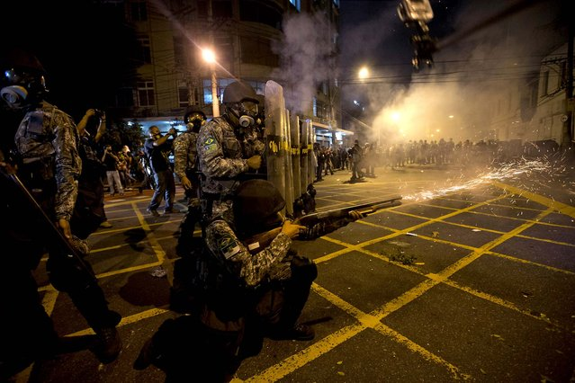 Military police fire tear gas at protestors near Maracana stadium while Brazil and Spain play in the Confederations Cup final, on June 30, 2013. (Photo by Silvia Izquierdo/Associated Press)