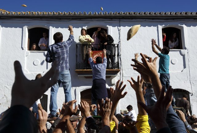 People try to catch pieces of bread thrown from a house during the annual San Antonio Abad (Saint Anton Abbott) festival in Trigueros, southwest Spain, January 25, 2015. Thousands of people arrived in Trigueros to participate in this annual catching of food and presents, part of a traditional three-day religious festival. (Photo by Marcelo del Pozo/Reuters)