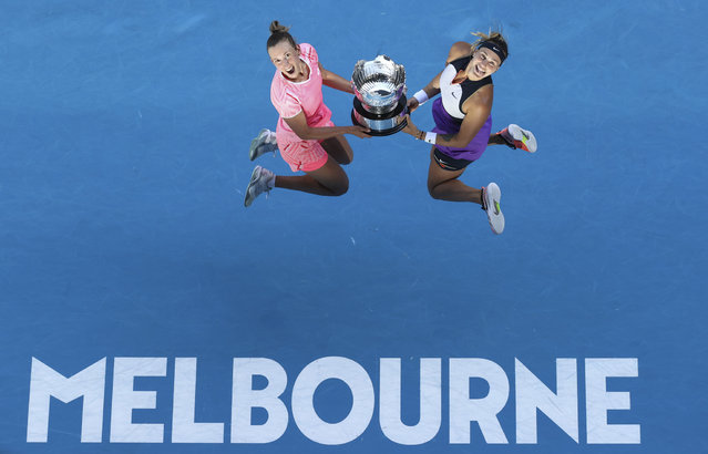 Belgium's Elise Mertens, left, and Aryna Sabalenka of Belarus celebrate with their trophy after defeating Barbora Krejcikova and Katerina Siniakova of the Czech Republic in the women's doubles final at the Australian Open tennis championship in Melbourne, Australia, Friday, February 19, 2021. (Photo by Hamish Blair/AP Photo)
