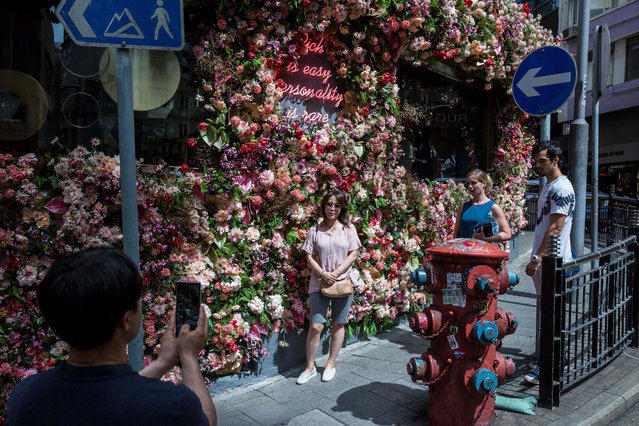 A women (C) poses for a photo in front of a business that has been decorated in fake flowers in the central district of Hong Kong on June 20, 2018. (Photo by Isaac Lawrence/AFP Photo)