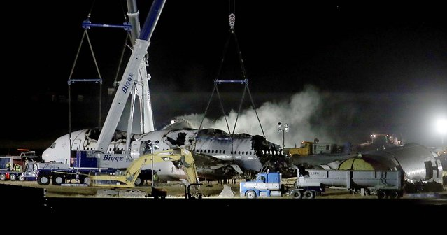 Asiana flight 214 is dismantled and hauled to a hangar at San Francisco International Airport, on July 12, 2013. Two people were killed and over 180 injured when the Boeing 777 crashed July 6 as it struck the seawall on the approach to runway 28L, knocking off the plane's tail. (Photo by Jane Tyska/Bay Area News Group)