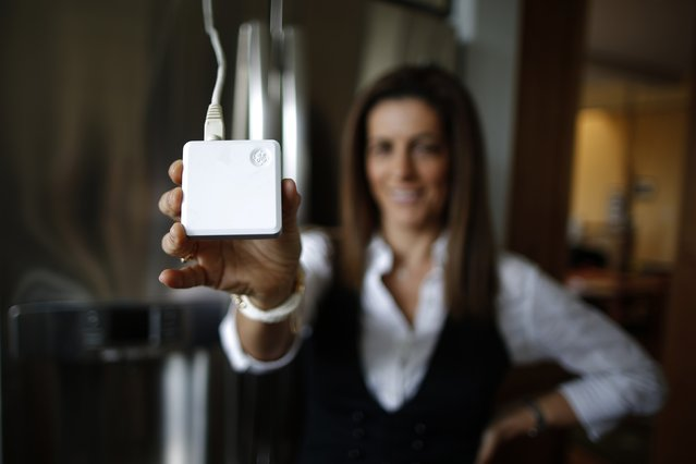 Computer science professor Christa Lopes holds an appliance communication module attached to the refrigerator in her home in Irvine, California January 26, 2015. Lopes said the Irvine Smart Grid Demonstration, a $79 million project funded half by federal stimulus money and half by Edison and partners like UC Irvine, cut her electric bill to zero in the summer. (Photo by Lucy Nicholson/Reuters)