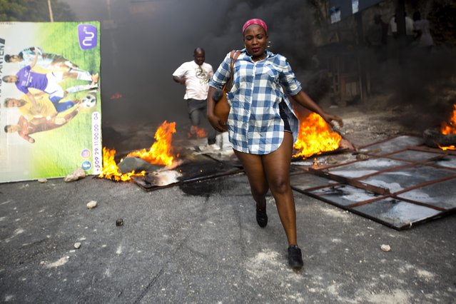 People run past a barricade set up and burned during a protest over the cost of fuel in Port-au-Prince, Haiti, Friday, July 6, 2018. Major protests erupted Friday in Haiti as the government announced a sharp increase in gasoline prices, with demonstrators using burning tires and barricades to block major streets across the capital and in the northern city of Cap-Haitien. (Photo by Dieu Nalio Chery/AP Photo)