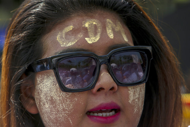 "An anti-coup protester with thanaka, a traditional face paste with letters CDM, representing ""Civil Disobedience Movement"" shouts slogans during a street march in Mandalay, Myanmar, Thursday, February 25, 2021. Protesters against the military's seizure of power in Myanmar were back on the streets of cities and towns on Thursday as regional diplomatic efforts to resolve Myanmar's political crisis intensified Wednesday. (Photo by AP Photo/Stringer)"