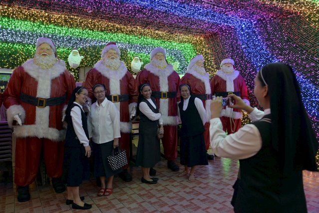 Catholic nuns have a picture taken next to Santa Claus statues inside a house decorated with Christmas lights in Cainta, Rizal province, north of Manila December 21, 2015. (Photo by Ezra Acayan/Reuters)