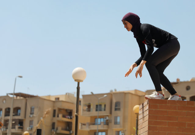 """An Egyptian woman from Parkour Egypt """"PKE"""" practices her parkour skills around buildings on the outskirts of Cairo, Egypt on July 20, 2018. Parkour is played by men in Egypt but the sport is neglected and has no regulatory body. Parkour Egypt, a group that comprises men and women, has grown exponentially after starting off with a handful of players. (Photo by Amr Abdallah Dalsh/Reuters)"""