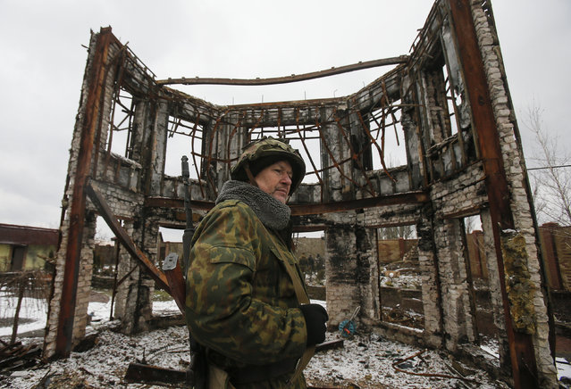 A member of the armed forces of the separatist self-proclaimed Donetsk People's Republic looks on near a building destroyed during battles with the Ukrainian armed forces in Vuhlehirsk, Donetsk region, February 4, 2015. (Photo by Maxim Shemetov/Reuters)