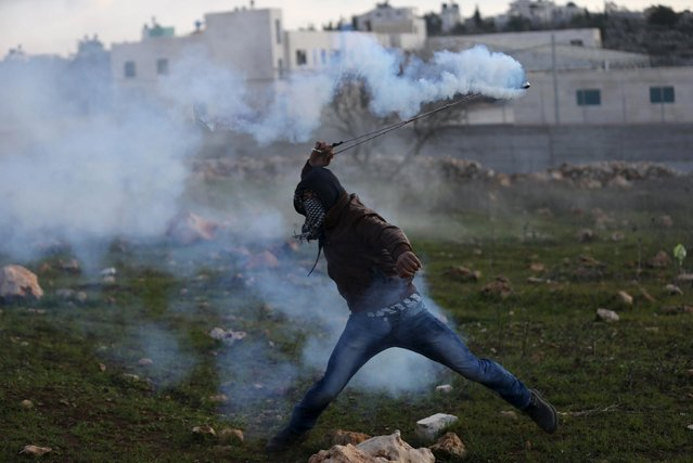 A Palestinian protester returns a tear gas canister fired by Israeli troops during clashes in the West Bank village of Silwad, near Ramallah December 26, 2015. (Photo by Mohamad Torokman/Reuters)