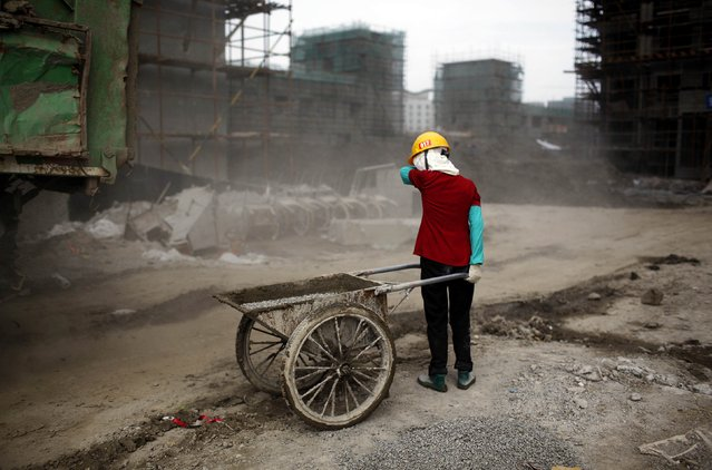 Ou Mei, a 45-year-old female migrant construction worker, shields her face from dust during a shift at a residential construction site in Shanghai in this July 2, 2013 file photo. China's slowing economy is making it harder for Beijing to mend holes in its pension system for the country's 268 million migrant workers. (Photo by Aly Song/Reuters)