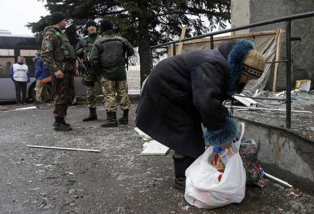 A woman looks through a bag of humanitarian aid as Ukrainian servicemen stand guard near a delivery point in the government forces-controlled town of Debaltseve, Donetsk region February 6, 2015. (Photo by Maxim Shemetov/Reuters)