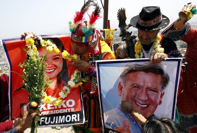 Peruvian shamans holding posters of Peru's presidential candidates Keiko Fujimori and Cesar Acuna perform a ritual of predictions for the new year at Morro Solar hill in Chorrillos, Lima, Peru, December 29, 2015. (Photo by Mariana Bazo/Reuters)