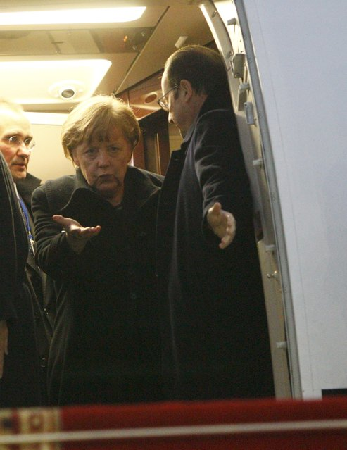 Germany's Chancellor Angela Merkel (L) and France's President Francois Hollande walk out after a meeting inside a plane at an airport near Minsk, February 11, 2015. (Photo by Valentyn Ogirenko/Reuters)