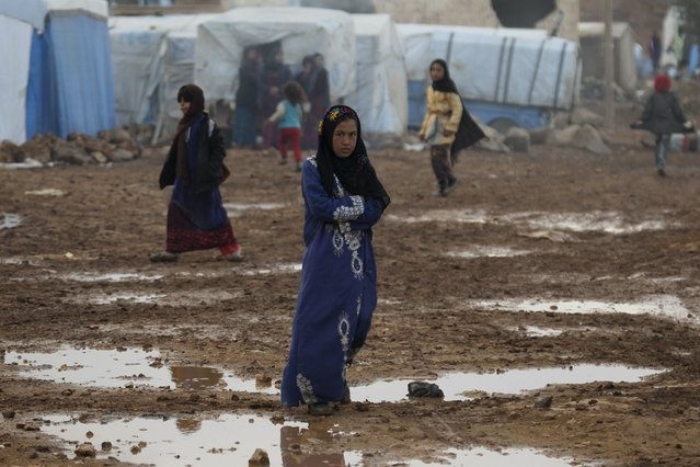 Internally displaced Syrians walk near puddles of water inside a refugee camp in the Hama countryside, Syria January 1, 2016. (Photo by Ammar Abdullah/Reuters)