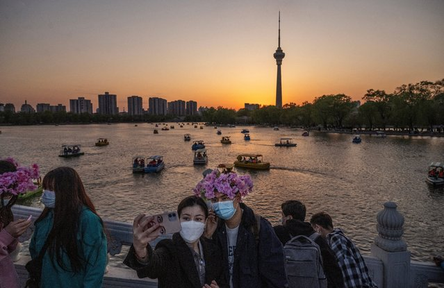 People take photos as tourist boats are seen in the water at a local park at sunset during the Qinming festival holiday on April 4, 2021 in Beijing, China. (Photo by Kevin Frayer/Getty Images)